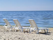 Three sun loungers on a deserted beach Royalty Free Stock Photography