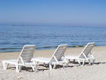 Three sun loungers on a deserted beach Stock Photography