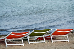 Three sunbeds on the beach Stock Images
