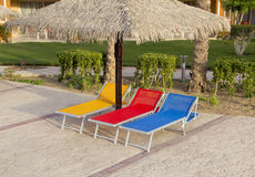 Three sunbeds near the swimming pool Royalty Free Stock Photos