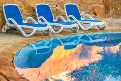 Three sunloungers reflected in blue water of the swimming pool Royalty Free Stock Photos