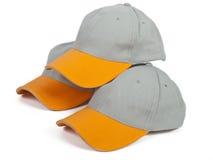 Three super caps. Three cool gray baseball caps with orange visor Royalty Free Stock Photos