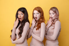 Three suprised ladies with crossed arms posing in studio. And covering their  mouthsover yellow background Royalty Free Stock Photos