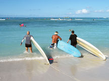 Three surfers enter the water in Honolulu Stock Photo