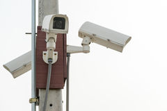 Three surveillance security cameras on white sky background Royalty Free Stock Photography