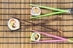 Three sushi rolls. With chopsticks on a bamboo mat Royalty Free Stock Photography