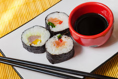 Three sushi rolls with chopsticks and a bowl of soy sauce. Three sushi rolls served on a rectangular plate with a bowl of soy sauce and chopsticks Stock Images