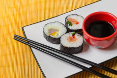 Three sushi rolls with soy sauce and chopsticks. A composition with three sushi rolls on a rectangular plate with a bowl of soy sauce and chopsticks, served on a Stock Image