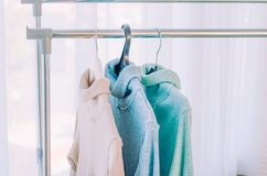 Three sweaters of pastel shades on hangers stock image