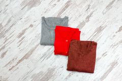 Three sweaters on a wooden background. Fashionable concept Stock Photography