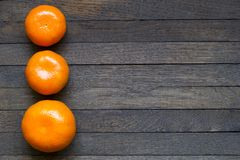 Few mandarins on dark brown wooden table with copy space. Three sweet bright orange tangerines on dark brown wooden table with copy space. Close up, top view royalty free stock photos