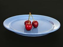 Three sweet cherries. On blue plate royalty free stock photo
