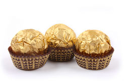 Three sweet chocolate bonbons in golden foil Royalty Free Stock Photos