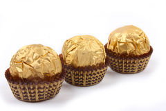 Three sweet chocolate bonbons in golden foil Royalty Free Stock Image