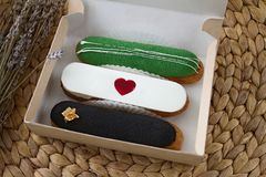 Three sweet delicious multicolored eclairs with a red heart in a cardboard box as a gift and a bouquet. Three sweet delicious multicolored eclairs with a red Stock Images