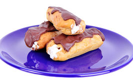 Three sweet  fresh Eclairs on blue plate Royalty Free Stock Image