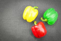 Three sweet pepper, yellow green and red, on dark textile background , top view royalty free stock photography