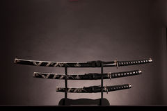 Three swords, B/W lighting. Copy space. Three ancient japanese swords with a monochrome lighting. Text can be inserted in the upper part of the image stock image