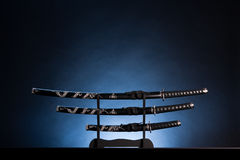 Three swords on blue background. Copy space. Three ancient japanese swords with a calm lighting. Text can be inserted in the upper part of the image stock image