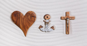 The three symbols of the devine trinity: heart, anchor, cross. Concept for religious items Stock Photography