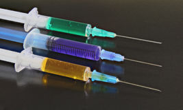 Three syringes on the black background Stock Photos