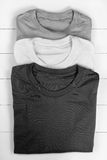 Three t-shirts. Three folded t-shirts. Converted in black and white Royalty Free Stock Photo