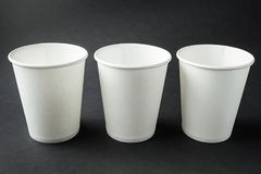 Three take away white paper cups for hot coffee, tea, juice and other beverages isolated on black. Retail mockup presentation royalty free stock photography