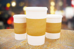 Three take out coffee cups. Disposable white paper coffee cups with blank brown labels on wooden table. Modern city background. Mock up, 3D Rendering Stock Photo