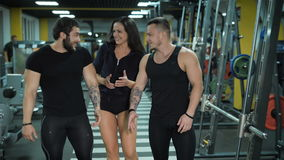 Three talking people walk at the gym. Three sporty happy people go at the gym and demonstrate wellness and health. Smiling girl and two men walk through the stock footage