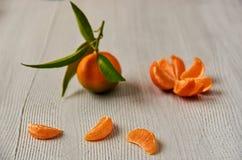 Three tangerine orange slices on the gray wooden board with free copy space. Peeled mandarin orange and fresh raw tangerine Royalty Free Stock Photo
