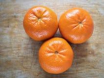 Three tangerine on wooden cut board. Top view on three tangerine on wooden cut board stock image
