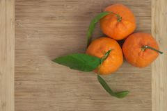 Three tangerines with leaves on wooden board Stock Photo