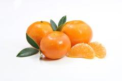 Three tangerines and a peeled chunks Royalty Free Stock Photo