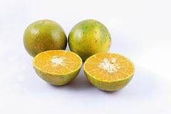 Tangerine [Thonburi]. The three tangerines split in a half on white background Royalty Free Stock Photo