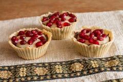 Three tartletes with custard and pomegranate Stock Photos