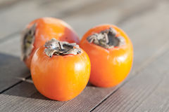 Three tasty persimmons on wooden table Royalty Free Stock Image