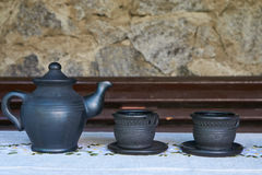 Three tea ceramic containers. One ceramic kettle and two ceramic tea mugs in a row on grey tablecloth. side profile view Royalty Free Stock Photography