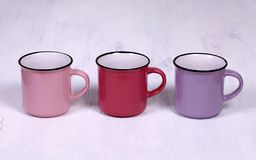 Three tea cups on white wood table background. Pink, red and purple mugs on white background royalty free stock images