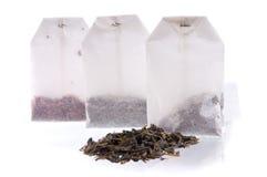 Three teabag and heap of black tea. Three teabags with dry tea and heap of black tea. Focus on a first teabag stock image