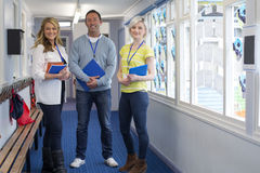 Three Teachers in School Corridor. Three teachers standing in the corridor of a school building. They are holding school work and smiling at the camera royalty free stock photography