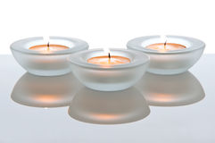 Three tealights with reflections Royalty Free Stock Images