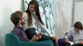 Employees relax on a chair in a hub, and pretty girl gently runs through the guy`s hair, smile and looking softly. Three team membres relax on a chair in a hub stock video footage