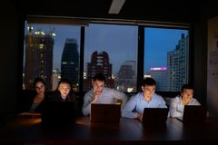 Three team working with computer overtime at night and low light royalty free stock image