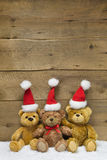 Three teddy bears with Christmas hats on wooden background Stock Image
