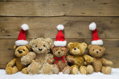 Three teddy bears with Christmas hats on wooden background Stock Photos