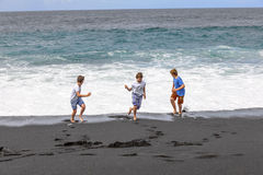 Three teen boys have fun at a black volcanic beach Stock Photo