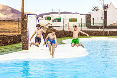 Three teen boys jumping in the pool Stock Image
