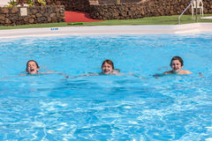 Three teen boys swimming in a pool. Three happy teen boys swimmin in a pool Royalty Free Stock Image