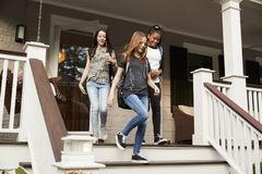 Three teen girls leaving house with school bags stock images