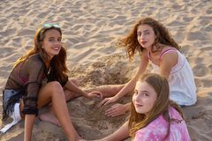 Three teen girls playing with the beach sand royalty free stock photo